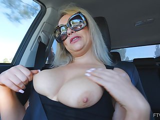 Amateur solo blonde MILF Elle masturbates in a car wearing glasses